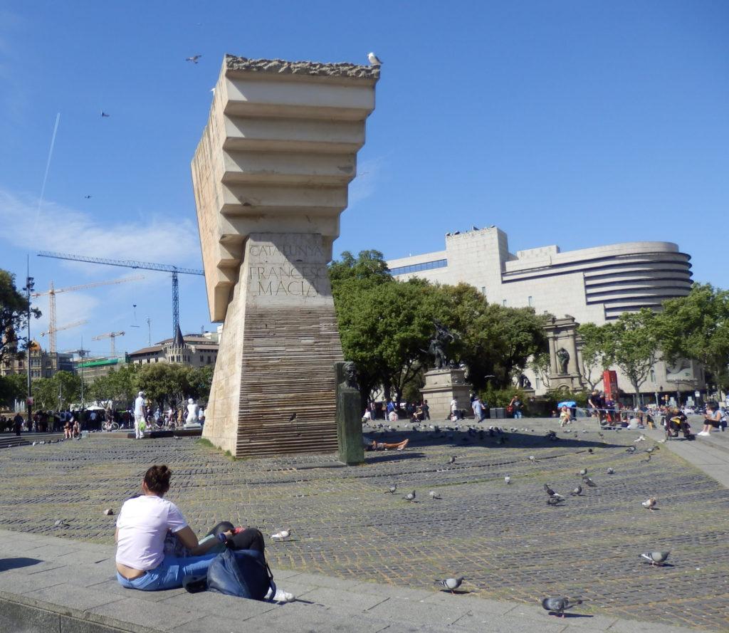 Skulptur Beton abgetreppt gegen den Beschauer im Brunnen, im Vordergrund junger Mann