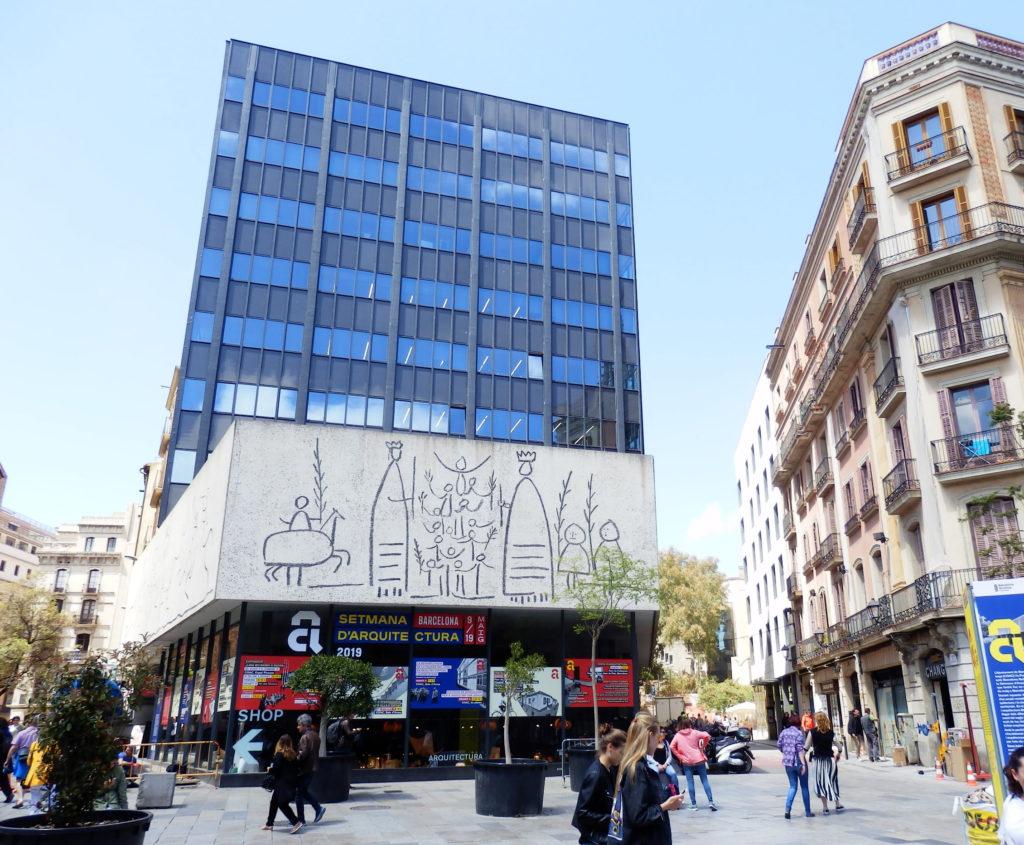 Hochaus Glasfassade über gößerem Sockelgeschoß aus Betonband mit Zeichnungnen nach Picasso, schwebend über Glasfassade des vertieften Untergeschosses