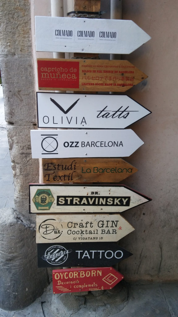 Wegweiser zu diversen Geschäften an Holzpfosten an einer Straßenecke in der Altstadt