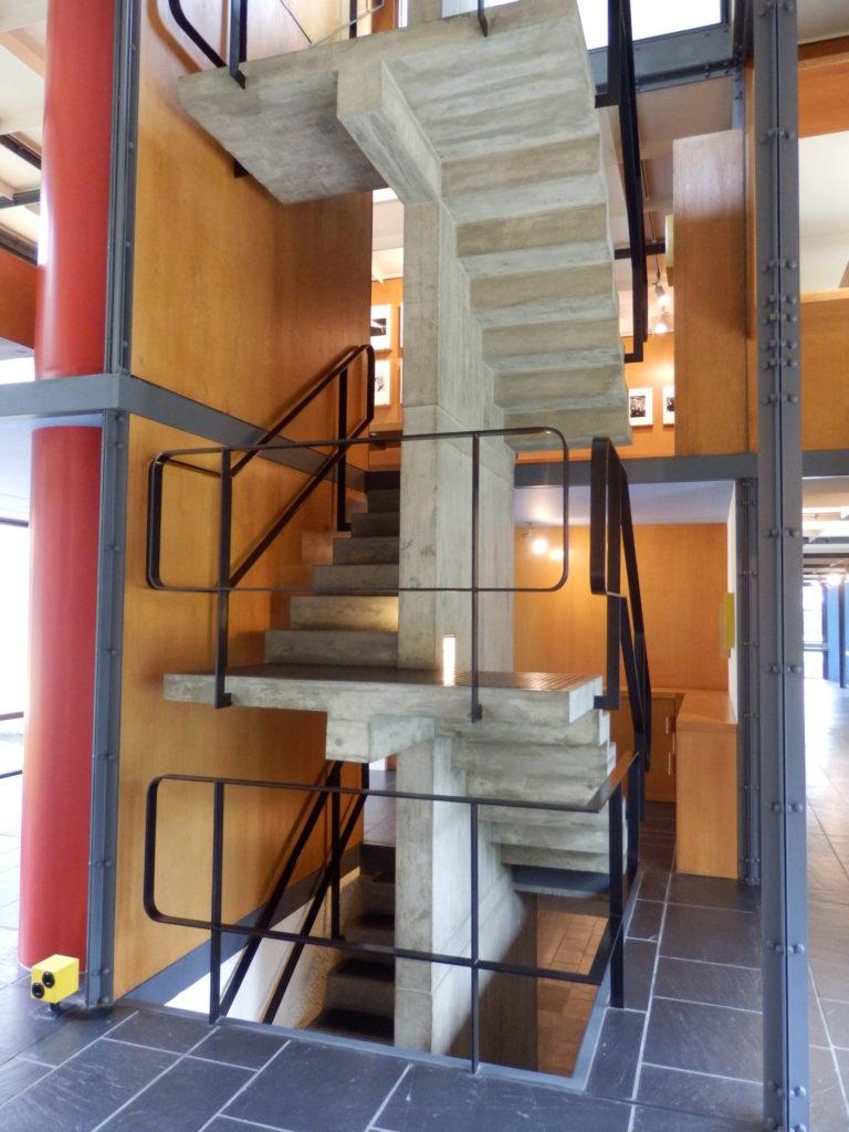 Schmale, freitragende Treppenläufe, Betonstruktur, mit schwarzem Stahl-Geländer vor gelben Wänden